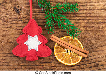 Red tree decoration with Christmas spices on wooden...