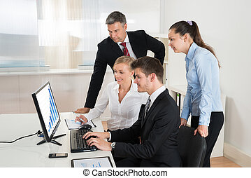 Businesspeople Looking At Graph In Office