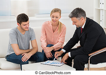 Financial Advisor Showing Graph To Couple - Mature Financial...