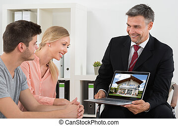 Estate Agent Showing House On Laptop To Couple - Mature...