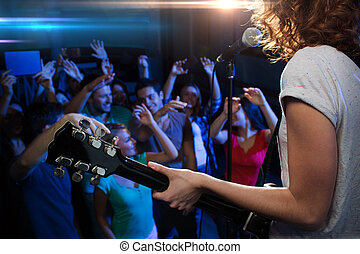 female singer playing guitar over happy fans crowd -...