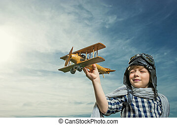 Dreamlike - Boy with wooden airplane outdoors