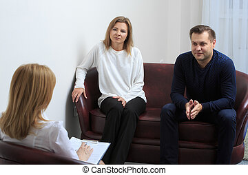 Therapist listening her patients and taking notes