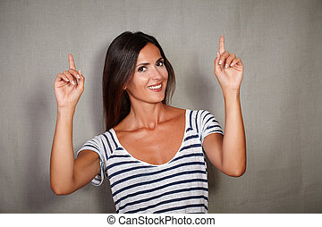 Happy woman pointing up while looking at camera