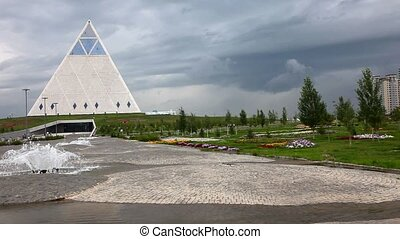 Pyramid, fountain, dramatic sky - Astana, Kazakhstan View of...