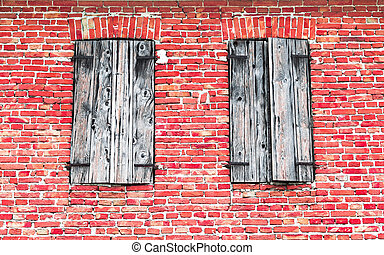 Windows with wooden frames on brick wall.