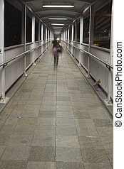 a woman walking on flyover to go home at night.