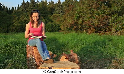 Young woman sitting in a park and reading a book, HD