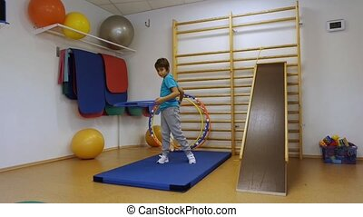 A young man using a hula hoop in her training in the gym