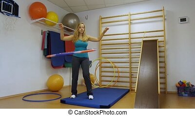 Woman using a hula hoop in her training in the gym