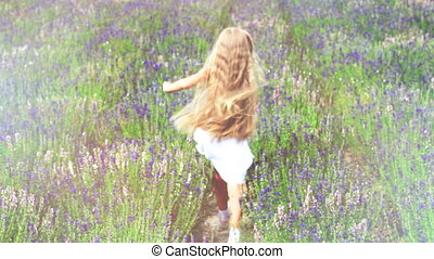 Cute girl escape from camera across the field. Child is in a white dress. Slow motion