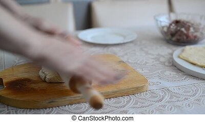 Womans hands unroll a dough for pelmeni - Womans hands...