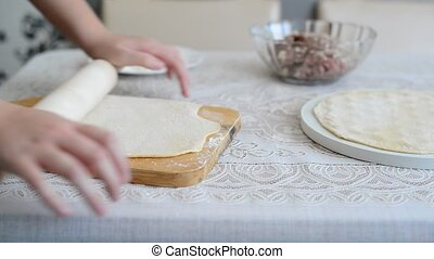 children's hands unroll a dough for pelmeni - children's...