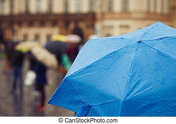 Rainy day - People with umbrellas in rain on the street -...