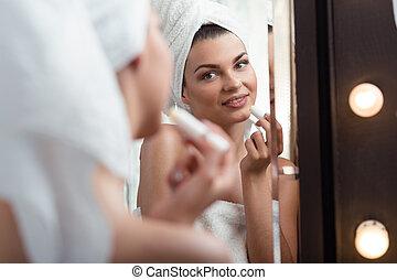 Smiling girl holding lipstick