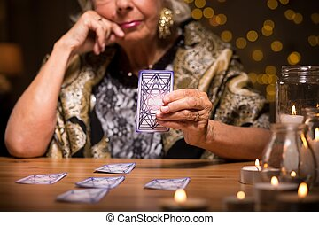 Telling fortune from tarot cards - Female seer telling...