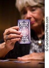 Tarot reader holding magic card - Elder female tarot reader...