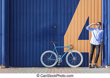 Businessman standing beside his bicycle and waiting for...