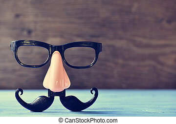 fake mustache, nose and eyeglasses on a blue surface - a...