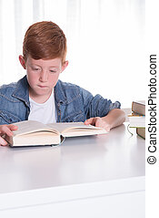 young boy reads very concentrated in a book