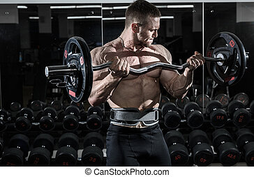 Athlete muscular bodybuilder in the gym training biceps with...