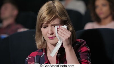 Girl with blue eyes crying during the movie