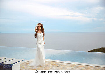 Beautiful bride girl in beaded wedding dress Summer holiday...