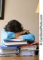 Too much work - Woman in despair with head on arms on a pile...