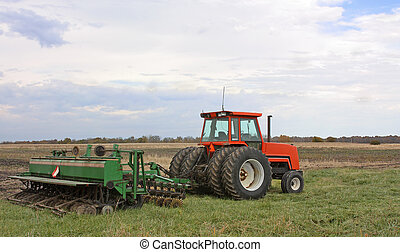 Tractor and Disc - Red farm tractor and disc in a field