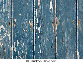 Blue flaky paint on a wooden fence.