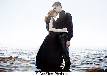 beautiful young couple hugging standing in the sea, photo...