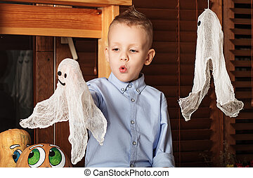 Halloween party with child holding toy ghost. Cute Little...