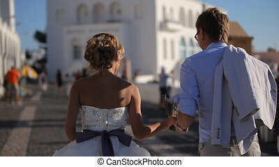newlywed couple running through the streets on the island of...