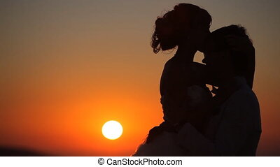 couple embrace on a background of a sunset - couple at...
