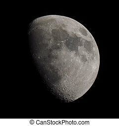 Gibbous moon over dark black sky seen with a telescope from...