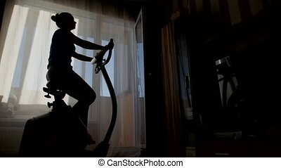 Woman exercising at home with a stationary bicycle