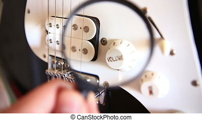 Inspecting Electric Guitar Details Over Magnifying Glass -...