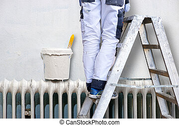 Man painting wall - Man on stepladder painting wall Plastic...
