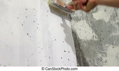 Paint the white concrete wall with a brush.