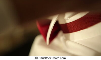 Bow tie - A man with a white shirt puts on a red bow tie