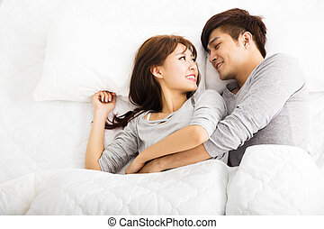 happy young lovely couple lying in a bed