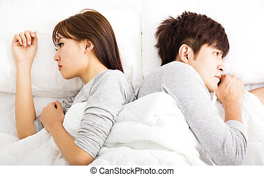Upset young couple  lying side by side in bed
