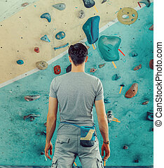 Man standing in front of a practical climbing wall - Young...
