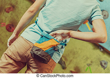 Climber woman with bag of magnesia - Climber woman putting...