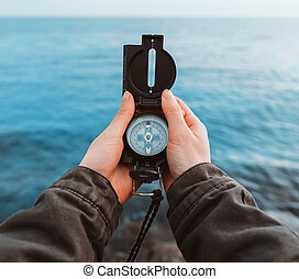 Tourist searching direction with a compass on coast