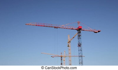 Cranes Working on Construction Site Under Clear Blue Sky Timelapse