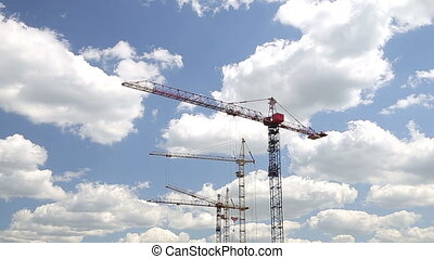 Cranes Working on Construction Site Under Cloudy Sky Timelapse
