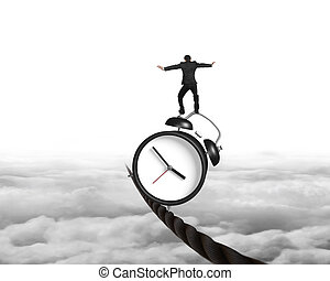 Businessman balancing alarm clock on tightrope, with sky...