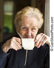 Old woman sits drinking tea