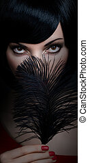 Fashion beauty portrait of brunette woman with black feather